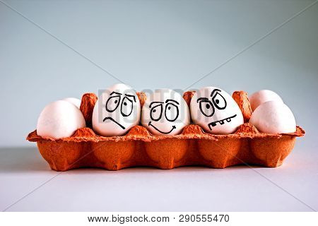 Funny Chicken White Eggs With Faces In An Egg Cell. Sad, Funny And Evil Egg. Easter Background.