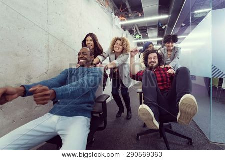 multiethnics startup business team of software developers having fun while racing on office chairs,excited diverse employees laughing enjoying funny activity at work break,
