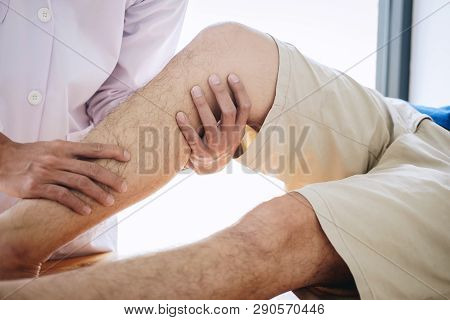 Doctor Physiotherapist Assisting A Male Patient While Giving Exercising Treatment Massaging The Leg