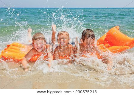 Happy children having fun on a beach splashing water laying on inflatable mattress enjoying summer vacation, clear sea water is seen in background