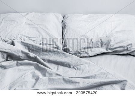 Messy Gray Bed Linen. Bed With Two Pillows In Daylight.