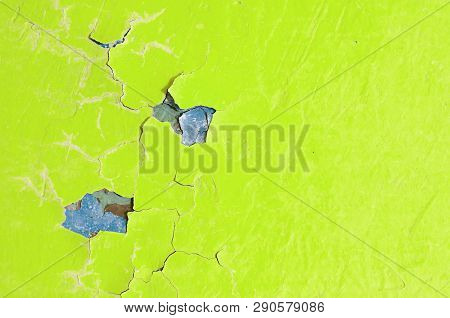 Texture background - bright yellow peeling paint on the old rough surface, close up of peeling paint texture on the old  texture background. Grunge texture surface with yellow peeling paint