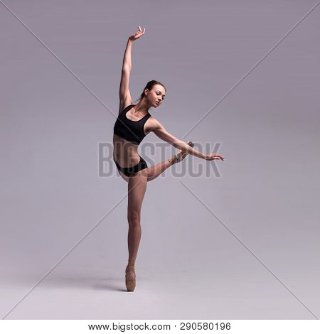 Beautiful Woman Ballet Dancer In Black Swimsuit Posing On Pointes Isolated On Light Grey Studio Back