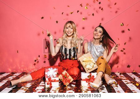 Portrait of two cheeky women 20s in stylish outfit celebrating and sitting on floor with bunch of present boxes isolated over red background