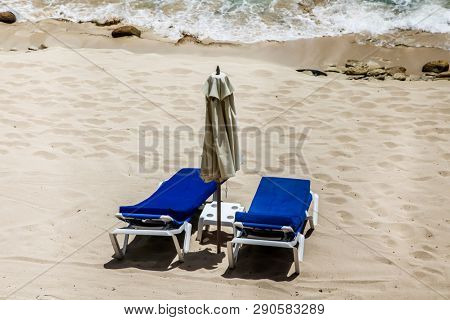 Two Beach Loungers and ocean with sand