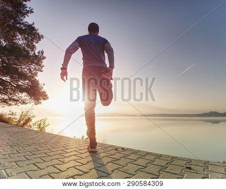 Man Runner Doing Stretching Exercise, Preparing For Morning Workout In The Lake Park. Street Fitness