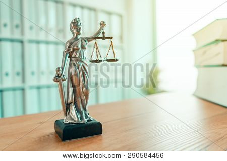 Lady Justice statue in law firm attorney office, blindfolded Justitia with balance scales and sword is personification of moral force in judicial system poster