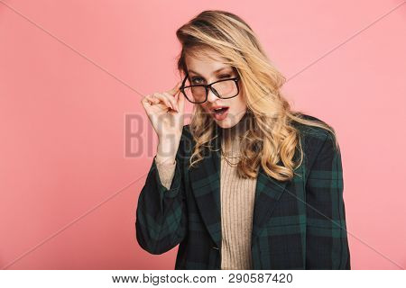 Portrait of cheeky blond woman 30s in stylish outfit and eyeglasses looking on camera isolated over red background poster