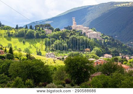 An image of Camerino in Italy Marche over colourful fields