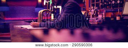 Bartender maintaining records at the counter in bar