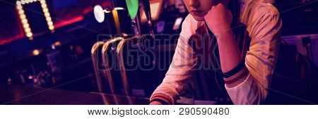 Female bartender using digital tablet while maintaining records at the counter in bar