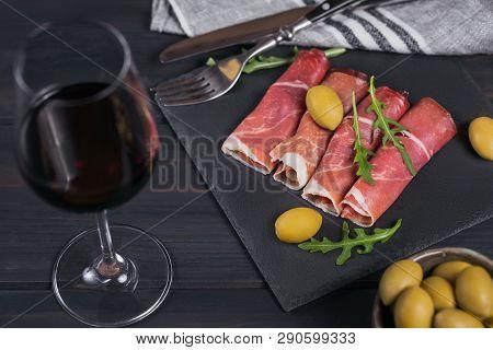 Black Stone Platter With Slices Of Cured Ham Or Spanish Jamon Serrano Or Italian Prosciutto Crudo Wi
