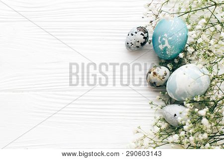 Happy Easter. Stylish Easter Eggs With Spring Flowers Border, Flat Lay On White Wooden Background Wi