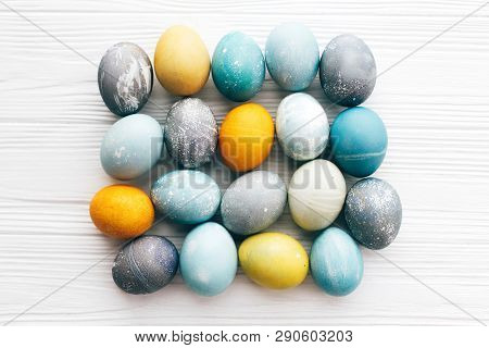 Stylish Easter Eggs Composition, Flat Lay On White Wooden Background. Modern Colorful Easter Eggs Pa