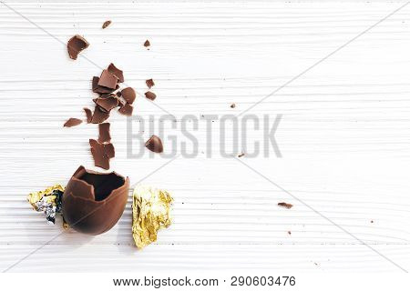 Stylish Easter Chocolate Egg Broken In Golden Foil With Chocolate Pieces On White Wooden Background,