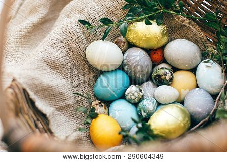 Stylish Easter Eggs And Green Buxus Branches In Rustic Wicker Basket On White Wooden Background. Mod