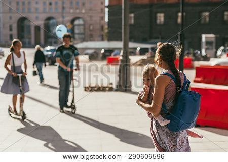 Moscow, Russia - August 14, 2015. Young Mother With A Baby In A Sling In The Front And A Backpack Be