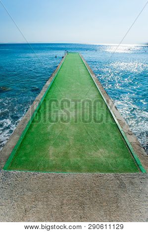 Green Pier Concrete Pier Over Blue Waters, Pier With Green Carpet