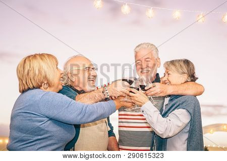 Happy Senior Friends Cheering And Toasting With Red Wine On Terrace - Older People Having Fun At Din