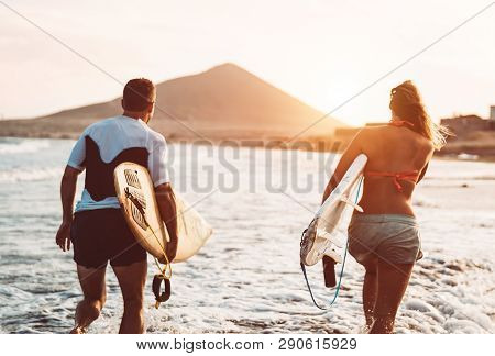Happy Surfer Couple Running With Surfboards Along The Sea Shore - Sporty People Having Fun Going To