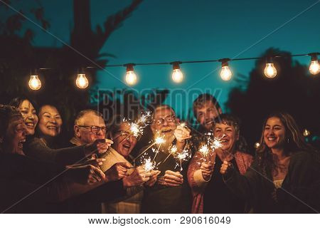 Happy Family Celebrating With Sparkler At Night Party Outdoor - Group Of People With Different Ages