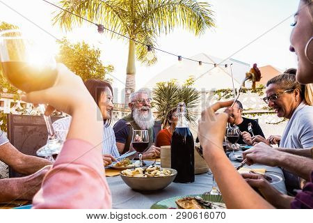 Happy Family Doing A Dinner During Sunset Time Outdoor - Group Of Diverse Friends Having Fun Dining