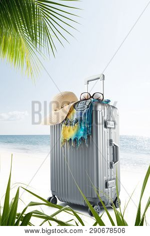 view of  suitcase with hat, pareo and sunglasses on sunny tropic beach poster