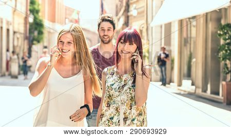 Young man following pretty women while having fun together on city street - Technology concept in everyday lifestyle with millenials people talking and using mobile smart phone - Bright filter poster