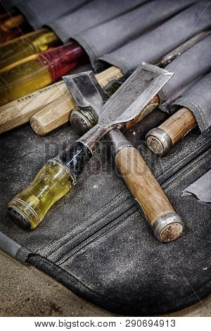 A grungy image of well used woodworking chisels in a chisel pouch poster