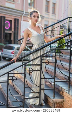 Young pretty brunette posing on the street holding on to the handrail standing on the steps dressed in a long dress poster