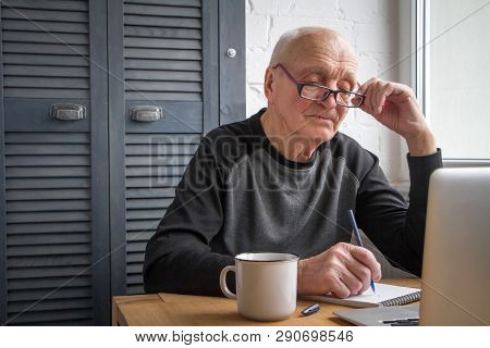 An Elderly Man Looks At The Laptop Screen, Makes Notes In A Notebook, Writes Taxes, Free Space For T