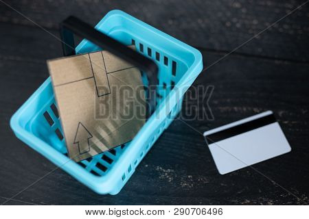 Cardboard Online Delivery Parcel In Shopping Basket And Payment Card Next To It