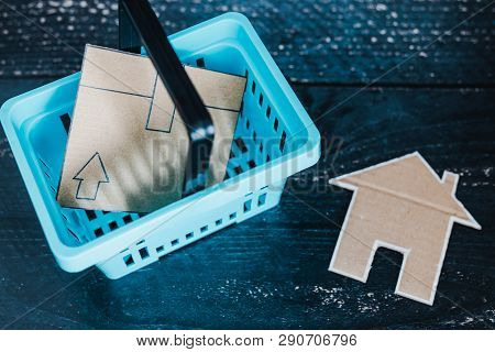 Buying Decor Items Or Furniture Concept: Shopping Basket With Parcel And Small Cardboard House Next