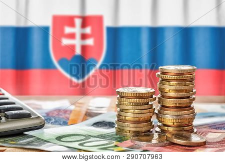 Euro Banknotes And Coins In Front Of The National Flag Of Slovakia