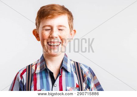 Portrait Of A Smiling Red-haired Boy With Freckles And Braces In A Checkered Shirt On A White Backgr