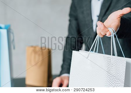 Shopping Reward. Loyalty Program. Checkout Man Presenting Paper Packet For Regular Customer.