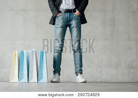 Shopping Time. Fashion Mans Legs In Jeans. Paper Bags Variety On Floor. Copy Space On Grey Backgroun