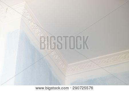 Decorative white cornice on blue wall, home room decor, design and architecture concept. poster