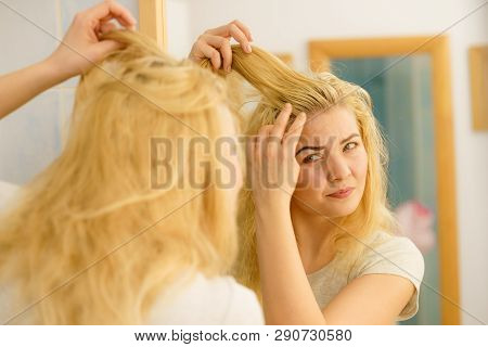 Blonde Woman Having Problems With Greasy Oily Hair Looking At Herself In Bathroom. Female Showing Sc