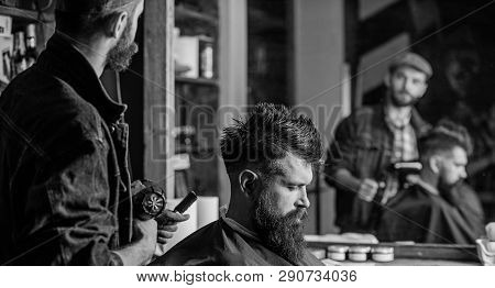 Hipster lifestyle concept. Barber with hairdryer works on hairstyle for bearded man barbershop background. Hipster bearded client getting hairstyle. Barber with hairdryer drying hair of client poster