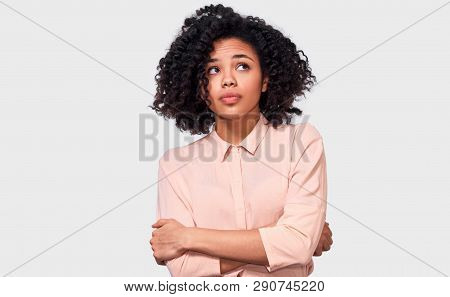 Thoughtful African American Woman Has Thinking Expression, Looking Up Away To The Blank Copy Space.