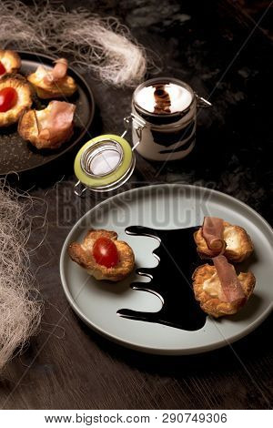 Vertical Photo Of Blue Plate With Puff Pastry Cups. Cups Are Stuffed By Melted Cheese. Ham And Red T