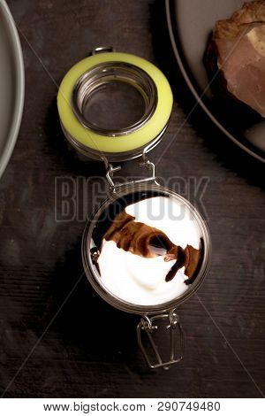 Glass Jar With Cover Full Of White And Brown Sauce On Dark Wooden Board