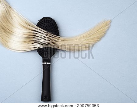 Close-up Of A Black Hair Brush And A Strand Of Blond Hair. Daily Hair Care Routine. Healthy Hair Or