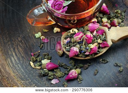 A Cup Of Tea. Green Tea With Flowers In A Wooden Spoon On A Dark Wooden Table. Green Tea With Flower