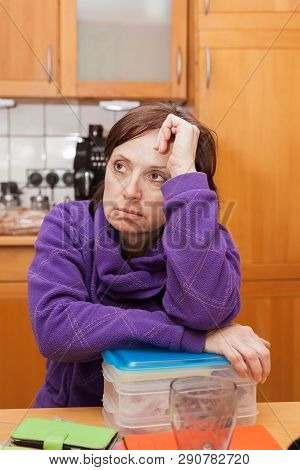 Middle-aging Woman Is Sitting Undecided In The Kitchen.