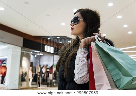 Profile Of Attractive Lady In Glasses And Fur Waistcoat Holding Many Shopping Bags At Mall Backgroun