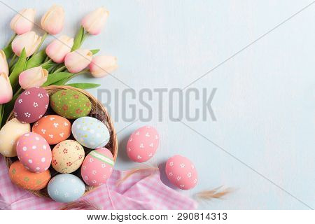 Happy Easter! Colourful Of Easter Eggs In Nest With Pink Tulips And Feather On Blue Sky Wooden Backg