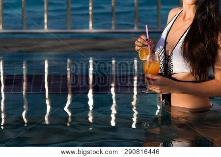 Woman With Long Dark Hair Wearing A White Swim Suit Holding A Cocktail Standing In A Pool With A Met
