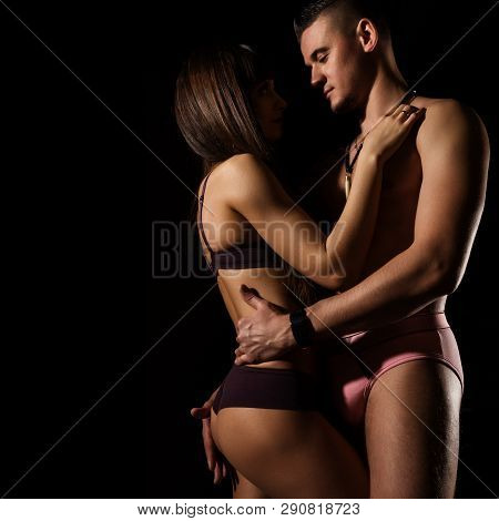 Seductive Portrait Of Pretty Sexy Couple In Love Hugs On Dark Background. Free Space For Your Text